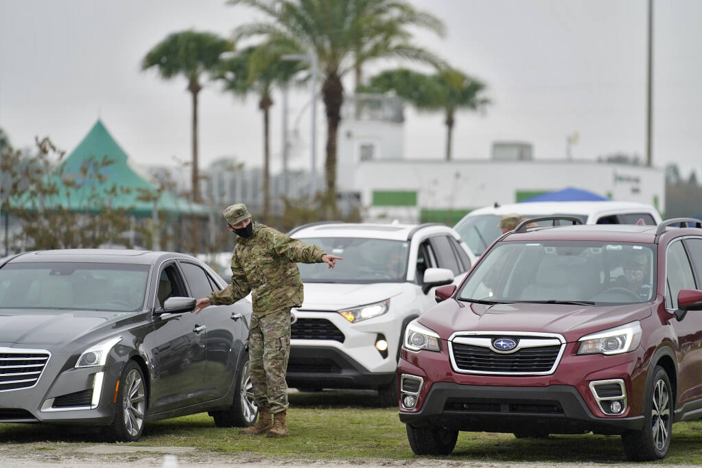 A member of the Florida National Guard directs people waiting in line for the coronavirus vaccine at an outdoor vaccination site at Lakewood Ranch Wednesday, Feb. 17, 2021, in Bradenton, Fla. (AP Photo/Chris O'Meara)