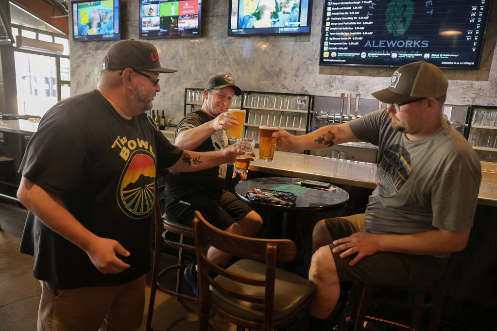 Dwayne Malone, left, Christian Velasquez, and Justin Brown have another round of beer at Third Street Aleworks in Santa Rosa on Monday, June 14, 2021.  The pub will be opening the bar and full capacity indoor seating Tuesday. (Christopher Chung/ The Press Democrat)