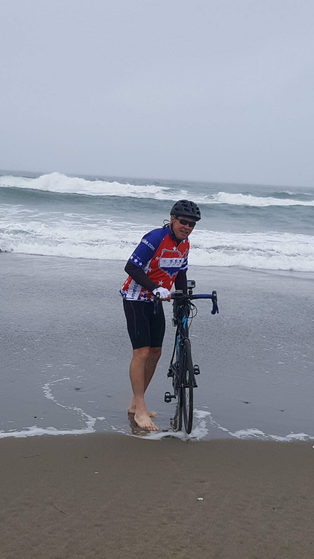SUBMITTED PHOTOPetaluman Doug Sanders dips his back wheel in the Pacific Ocean at the start of a 3,829-mile cross country ride.
