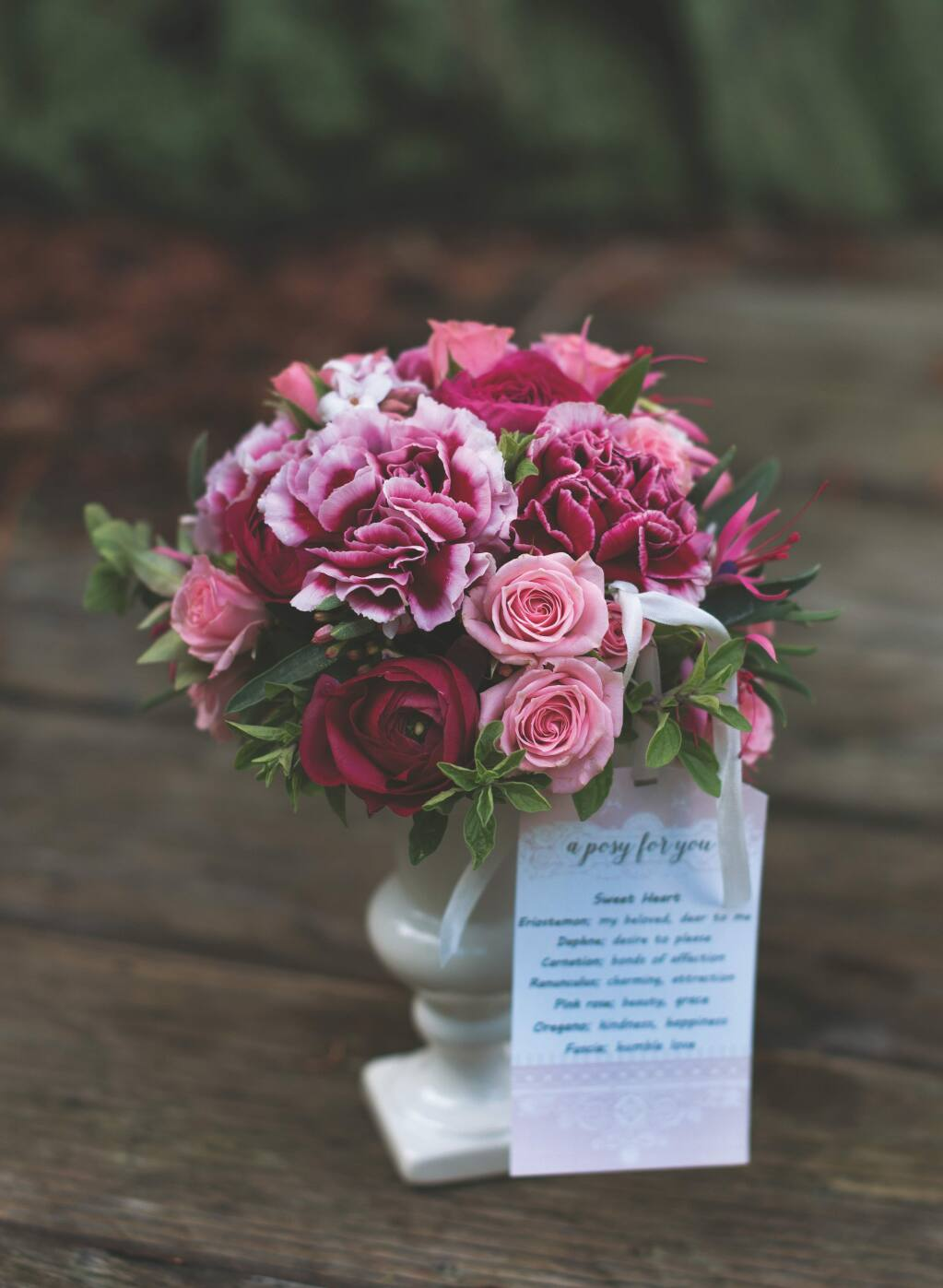 A posy is a small, round bouquet of flowers and herbs that are chosen based on their meanings to convey a message inspired by the Victorian-era language of flowers. Shown is a Sweet Heart Posy, given either to a daughter or a lover. It includes pink roses, fuschia, Eriostemon and Daphne. (Danyelle Dee)