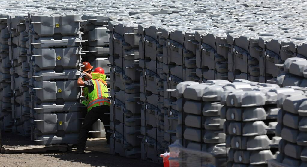 David Gomes, left, and Walker Rotherham unload solar panel floats that will be floated in to one Windsor's effluent ponds, Wednesday, June 5, 2019. (Kent Porter / The Press Democrat) 2019