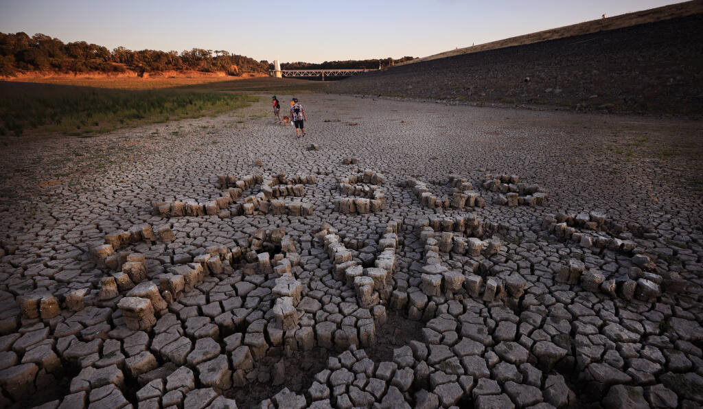 """At the foot of Coyote Valley Dam on the bottom of Lake Mendocino, someone spelled out """"Jesus Saves"""" with drought-cracked blocks of mud, Thursday, July 15, 2021 east of Ukiah. In the background are Ukiah residents Hannah Campion, Aven Bevilacqua and Jason Griego with their dog Apollo. (Kent Porter / The Press Democrat) 2021"""