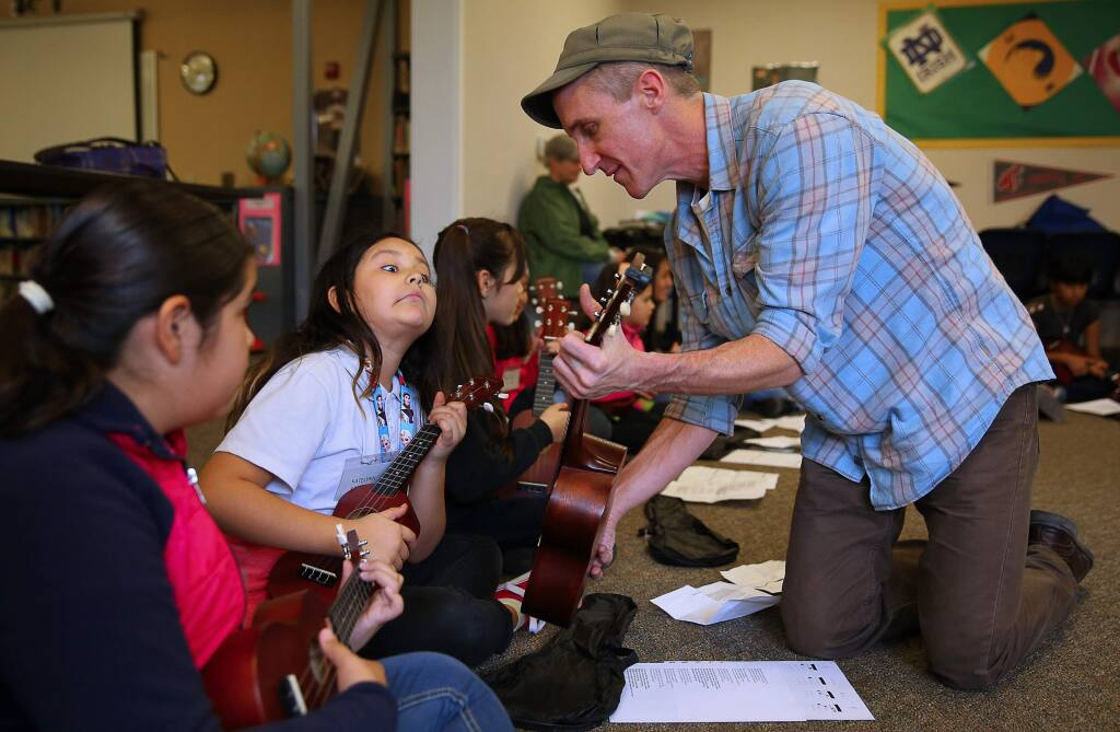 Music teacher Andrew DeVeny shows Katelynn Valencia the proper finger placement for a note while teaching students how to play the ukulele at Bellevue Elementary School in Santa Rosa, on Thursday, Jan. 21, 2016. The ukulele lessons were part of the Wells Fargo Center for the Arts' education outreach program, and students will be joining the Wellington International Ukelele Orchestra during a performance this week. (Christopher Chung / The Press Democrat)