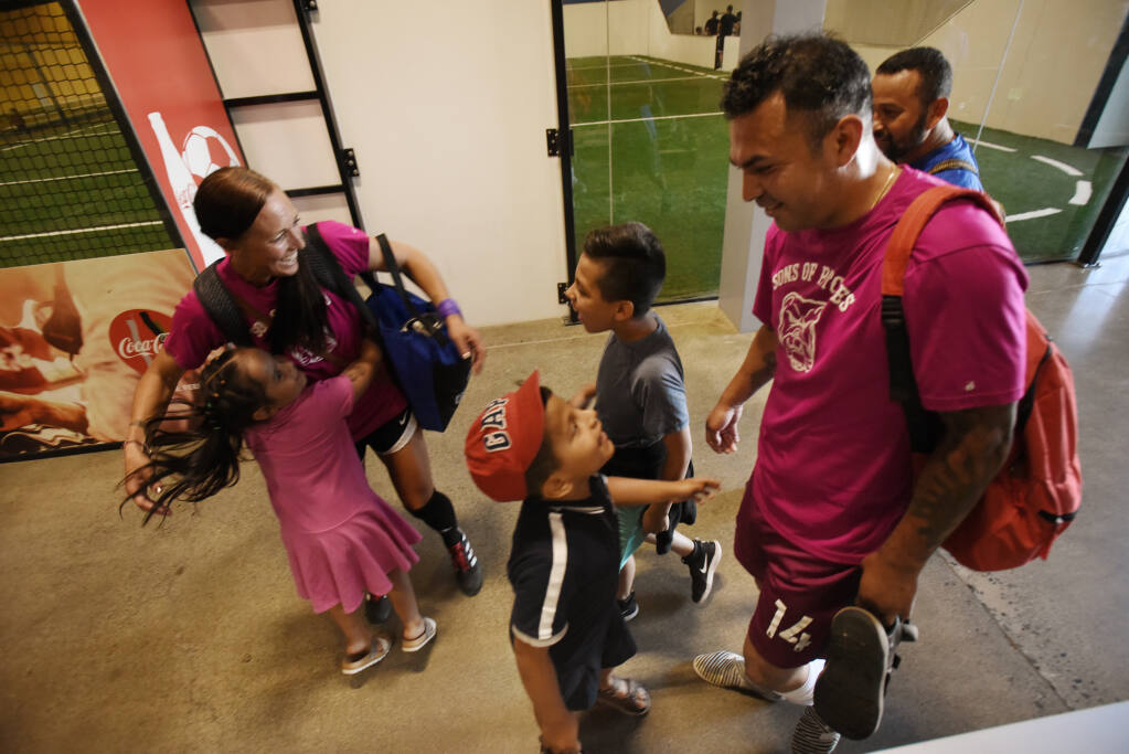 Sons Of Pitches player Roberto Hernandez, right, with his three children, from left, Dayra, 4, hugging fellow player Crystal Howard, Bernardo, 6, and Juan Pablo, 9, after an adult league indoor soccer game at Epicenter Sports and Entertainment in Santa Rosa, California on Friday, July 2, 2021. (Erik Castro/for The Press Democrat)