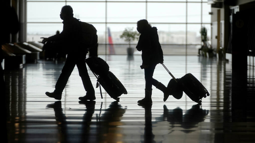 Travelers are shown in Salt Lake City International Airport Tuesday, March 9, 2021, in Salt Lake City. (AP Photo/Rick Bowmer)