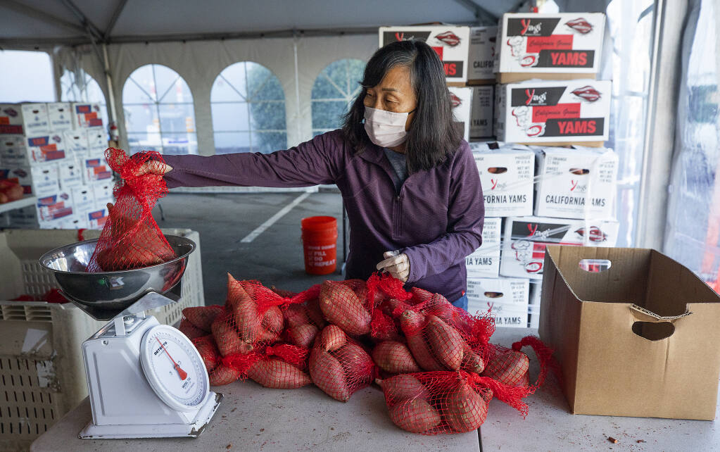 Volunteer Jeanne Allen weighs a bag of yams at the Redwood Empire Food Bank in Santa Rosa on Feb. 4, 2021. With demand for food continuing to soar amid the pandemic, the regional food bank is desperate for more volunteers.(Photo by John Burgess/The Press Democrat)