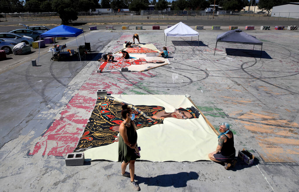 Joy Ayodele, left, views a mural of herself completed by SCAPE (Sonoma County Artists Propelling Equity) Tuesday, Aug. 4, 2020, in Roseland. Remi Newman, co-founder of SCAPE, is on the right. (Kent Porter / The Press Democrat) 2020