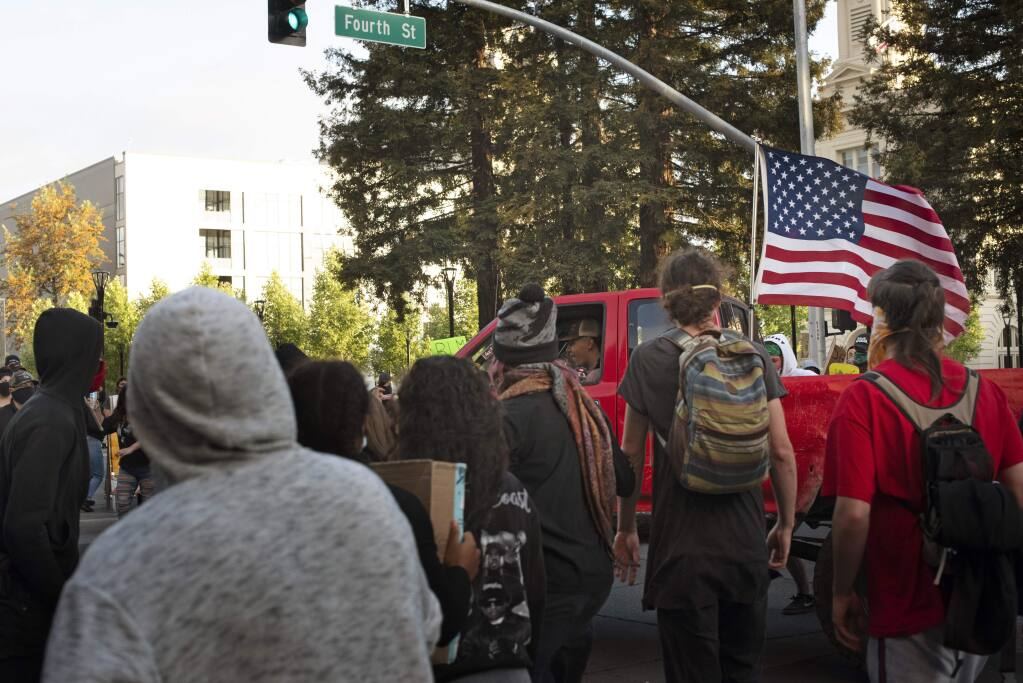 A group of protesters confront a truck with skateboards, water bottles and bare hands after the pickup drove through protesters on Fourth and Mendocino in downtown Santa Rosa on May 30, 2020. (Erik Castro/For The Press Democrat)