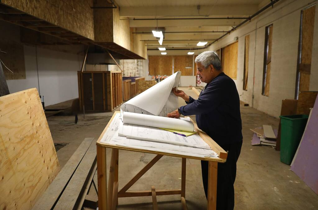 Miguel Gucho glances a plans for a new billiards hall, along Sebastopol Avenue, in the Roseland area of Santa Rosa on Wednesday, January 17, 2018. Gucho's plumbing business installed the fire sprinklers in the building.(Christopher Chung/ The Press Democrat)