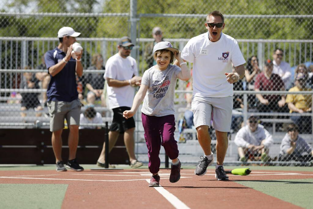 Violet Albrecht-Brown, 8, is cheered on by volunteer Mark Wolf as she runs towards first base after hitting the ball during the opening day celebration of the Miracle League field at Lucchesi Park in Petaluma, California on Sunday, April 14, 2019. (BETH SCHLANKER/The Press Democrat)