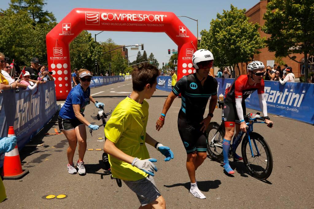 Triathletes Ignacio Lopez Mancisidor of Key Biscayne, Florida and Daniel Brook, far right, of Dubai enter the Bike to Run transition point during Ironman Santa Rosa in Santa Rosa, California, on Saturday, May 11, 2019. (Alvin Jornada / The Press Democrat)