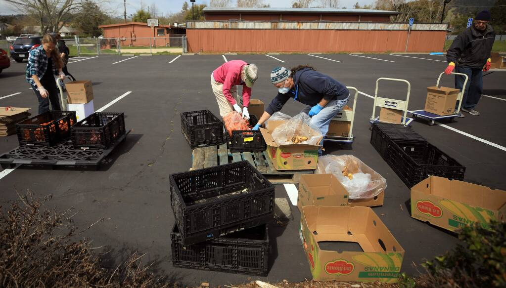 Volunteers with the Redwood Empire Food Bank, Friday, March 27, 2020, consolidate the last of the food during a drive through food giveaway in the parking lot of The Lighthouse Church in Rincon Valley. (Kent Porter / The Press Democrat) 2020