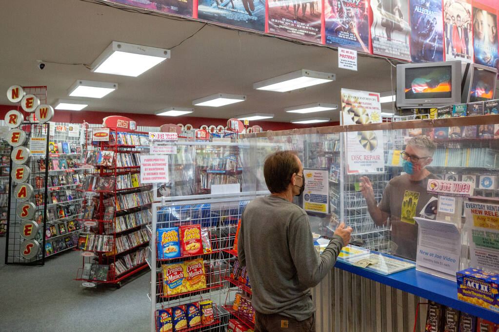 From behind a plexiglass barrier, Joe Kaminski, owner of Joe Video, chats with Michael Lott as he rents a selection of movies at Joe Video in Santa Rosa on Saturday, Oct. 24, 2020. (Alvin A.H. Jornada / The Press Democrat)