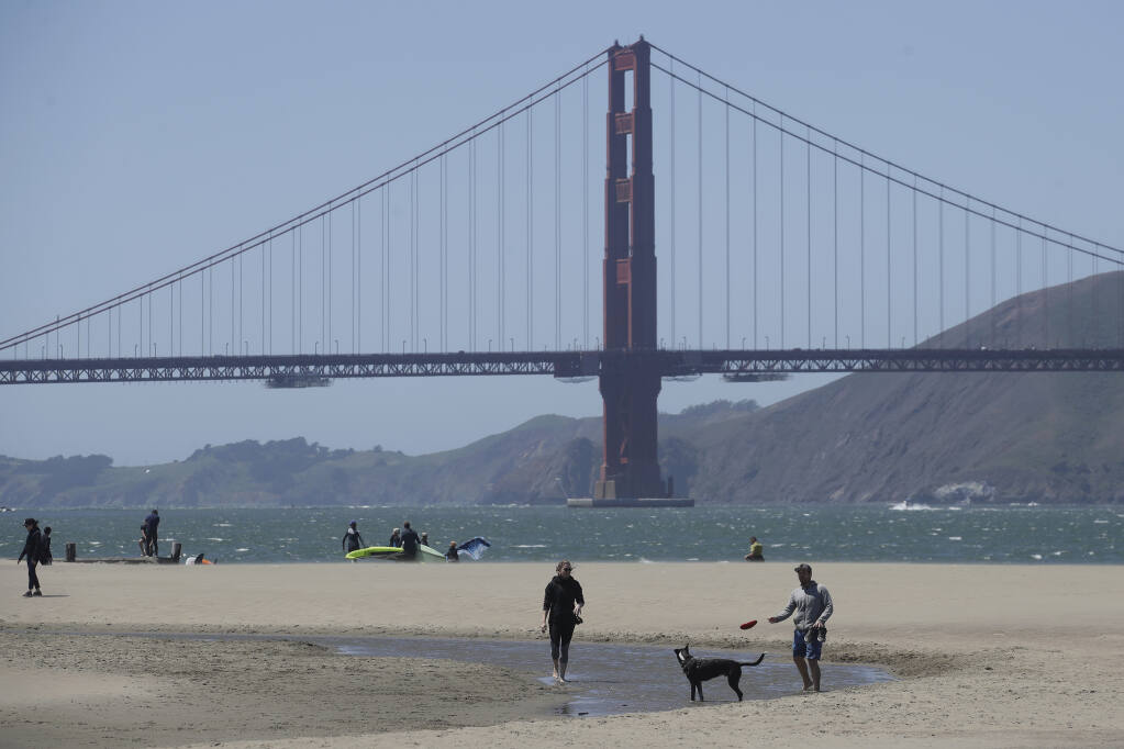 People walk on the sand in front of the Golden Gate Bridge at Crissy Field East Beach in San Francisco, Sunday, May 3, 2020, during the coronavirus outbreak.  (Jeff Chiu / Associated Press)