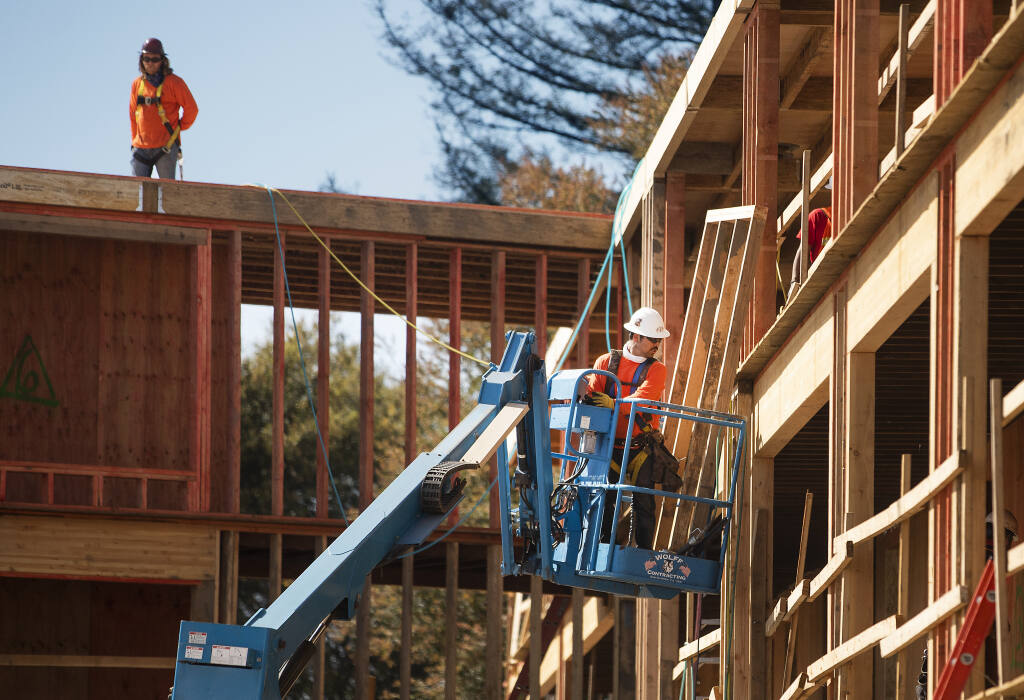 Workers install framing for columns in the 54-unit Sage Commons affordable housing project on the corner of College and Cleveland avenues in Santa Rosa on Tuesday, March 23, 2021. The project, along with the 46-unit Boyd Street Family Apartments, is being built by Danco Communities of Humboldt County. (John Burgess / The Press Democrat)