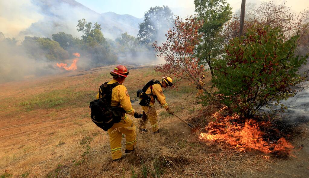 Cal Fire firefighters jump on a hot spot off Highway 20 in Lake County just east of Blue Lakes in 2014. (KENT PORTER/ PD FILE)