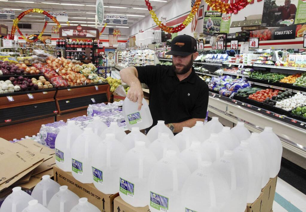 Chris Creel, manager of Piggly Wiggly, stocks pallets of bottled water as grocery customers prepare for the arrival of storm weather with Hurricane Dorian in New Bern, N.C., Wednesday, Sept. 3, 2019. New Bern is still recovering from the damages caused by Hurricane Florence in 2018. (Gray Whitley/Sun Journal via AP)