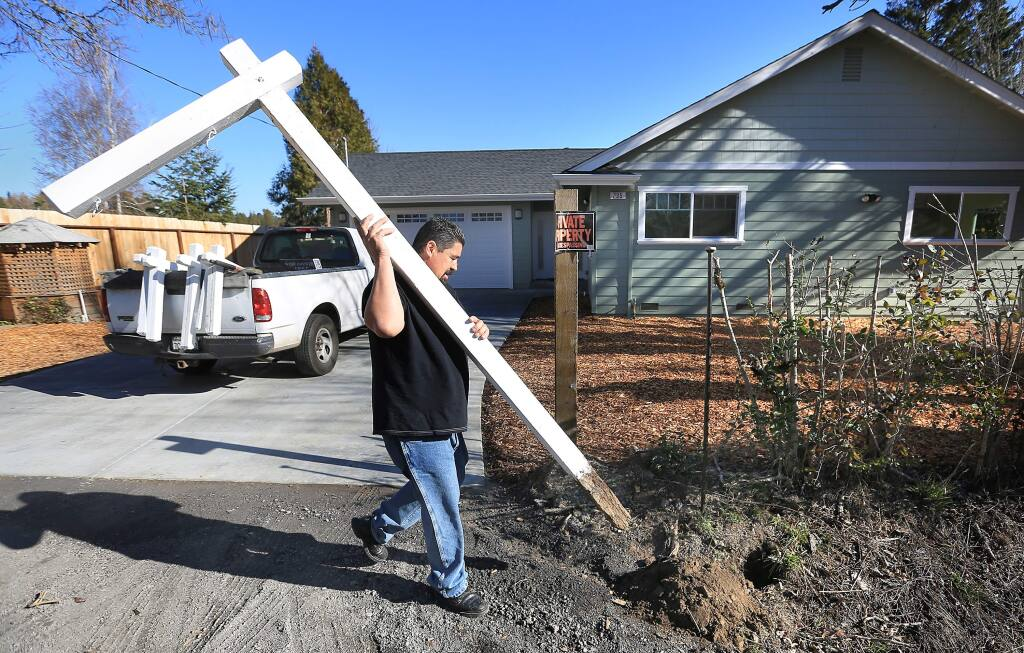 Roberto Valencia of North Bay Signs places a for sale sign post on Montgomery Road in Sebastopol, Wednesday Jan. 15, 2014. (Kent Porter / Press Democrat)