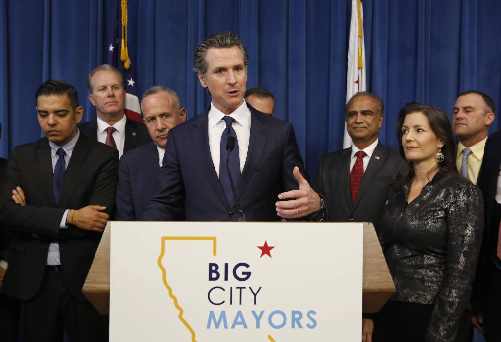 Gov. Gavin Newsom, center discusses the homeless problem facing California after a meeting with the mayors of some of the state's largest cities held at the Governor's office, Wednesday, March 20, 2019, in Sacramento, Calif. Newsom and the mayors are pushing for more money on top of the $500 million the state has already given cities for programs assisting the homeless. Accompanying Newsom are California mayors from left, Robert Garcia, of Long Beach, Kevin Falconer, of San Diego, Darrell Steinberg, of Sacramento, Harry Sidhu of Anaheim, Libby Schaaf, of Oakland and Rusty Bailey, of Riverside, right. (AP Photo/Rich Pedroncelli)