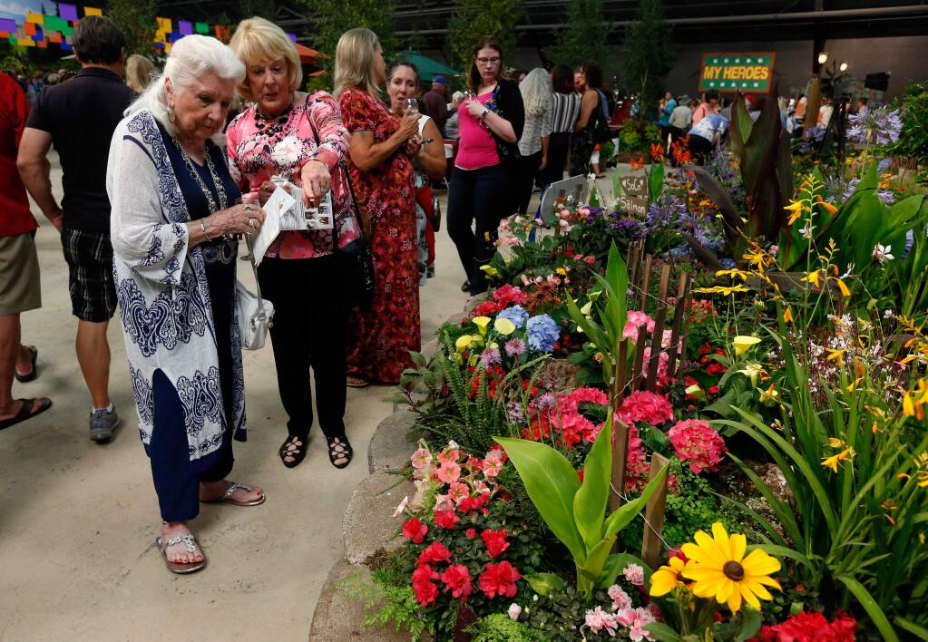 Gwen Adkins, left, and Wendy James, both of Santa Rosa, peruse the flowers in the Coastal Charisma display by botanical artist Daniel R. Gibbs, during the Hall of Flowers preview at the 82nd annual Sonoma County Fair in Santa Rosa, California, on Wednesday, Aug. 1, 2018. (ALVIN JORNADA/ PD)