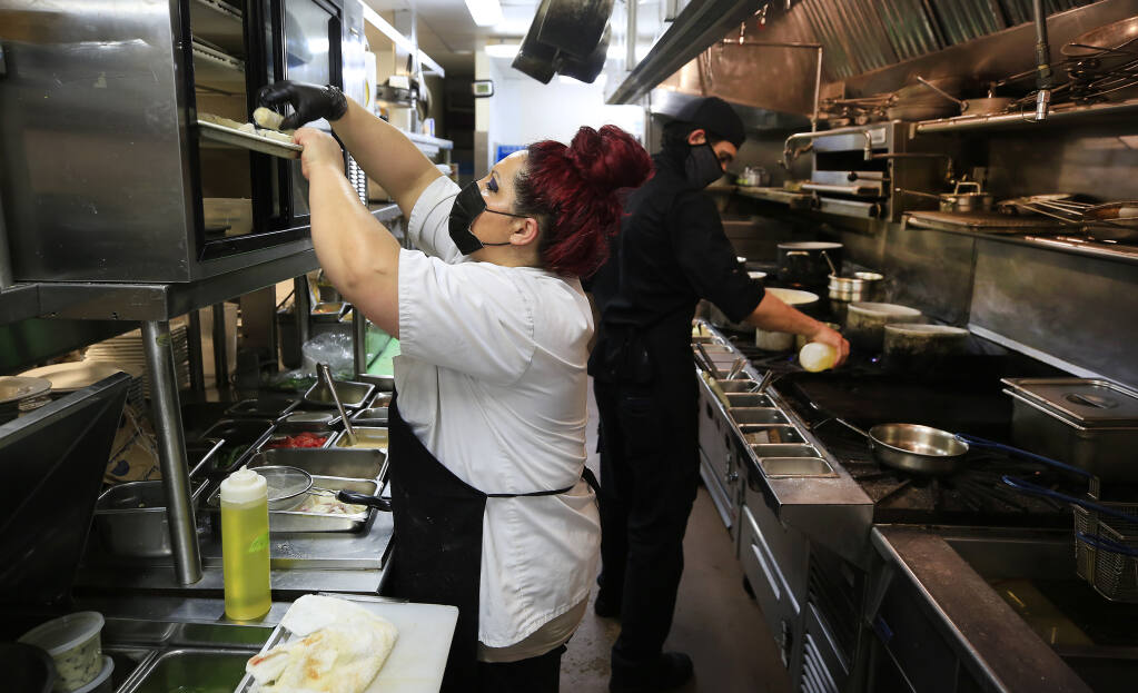 Arianna Sanchez, left, and Gino Guerrero prepare an incoming round of meals at John Ash & Co., Friday, April 23, 2021 in Santa Rosa.  (Kent Porter / The Press Democrat) 2021