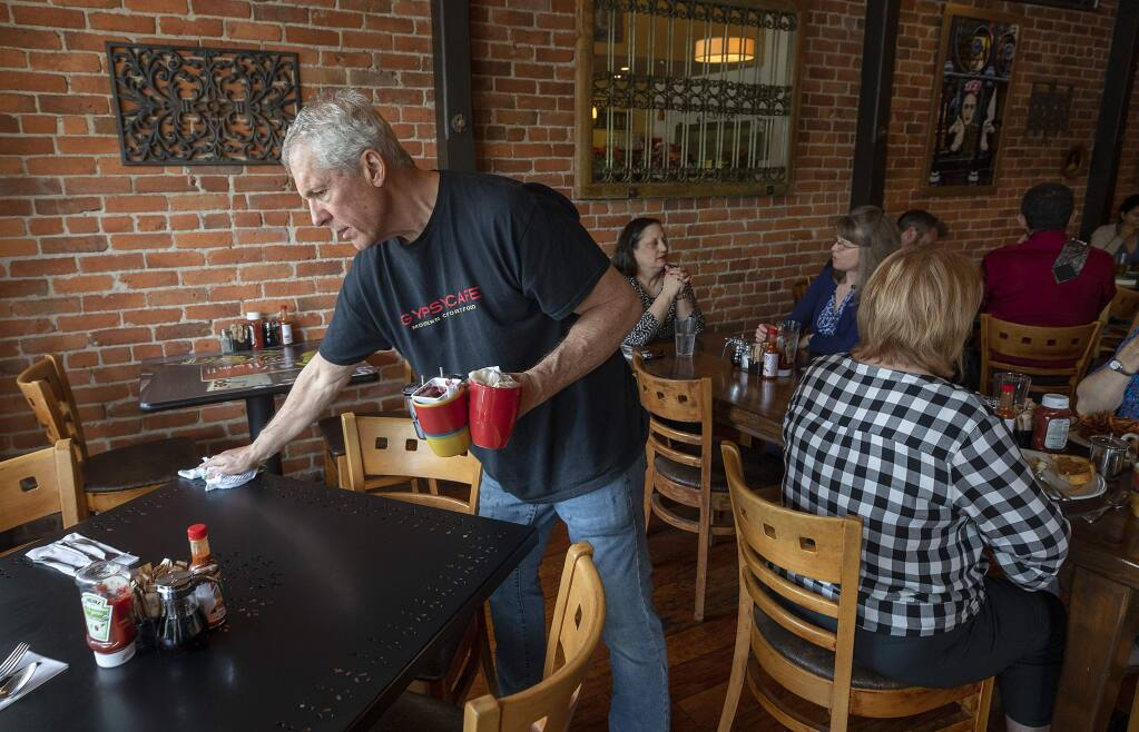 Rob Scheid wipes down a table on a crowded Friday morning at the Gypsy Cafe in Sebastopol. (photo by John Burgess/The Press Democrat)