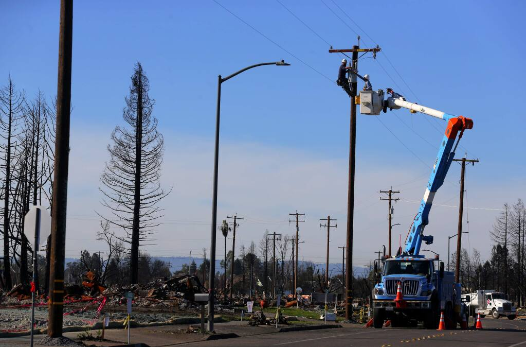 A PG&E crew works on power lines along Hopper Avenue, in the Coffey Park area of Santa Rosa on Thursday, Dec. 7, 2017. (Christopher Chung/ The Press Democrat)
