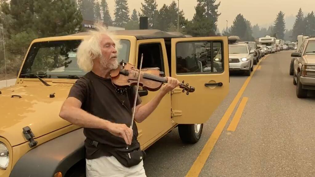 Mel Smothers of South Lake Tahoe plays violin to pass the time as traffic heading east on Highway 50 from South Lake Tahoe comes to a standstill. The backup came after authorities evacuated the entire city of South Lake Tahoe on Monday, Aug. 30, 2021 as the Caldor fire continued its march toward the lake. (Kent Porter / Press Democrat)