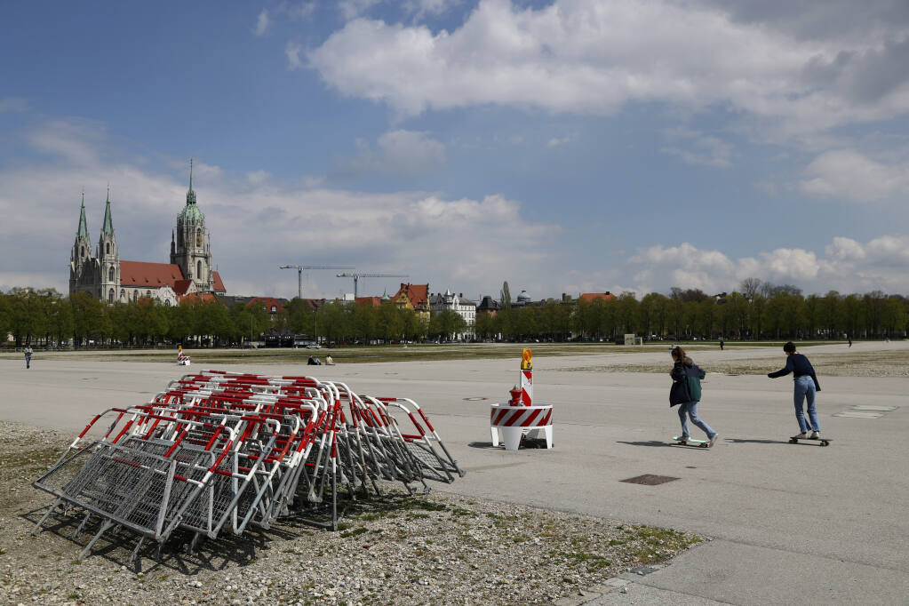 People skateboard in the Theresienwiese' area where the 'Oktoberfest' beer festival is held, in front of the St. Pauls church in Munich, Germany, Monday, May 3, 2021. The world's largest beer festival 'Oktoberfest' was cancelled last year due to the coronavirus outbreak. (AP Photo/Matthias Schrader)