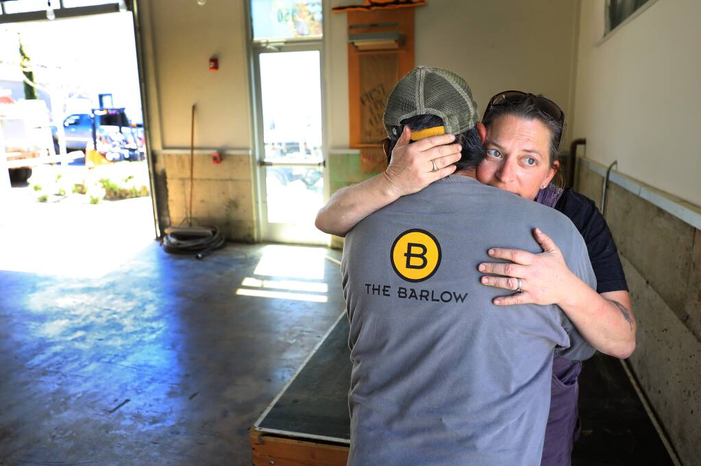 Zazu Kitchen and Farm Duskie Estes embraces Tomas Guzman, part of the maintenance crew of The Barlow, Thursday, April 18, 2019 in Sebastopol. Estes and her husband John Stewart pulled all of their equipment out of the restaurant on Thursday after February flooding of the Laguna shut them down. (Kent Porter / Press Democrat) 2019