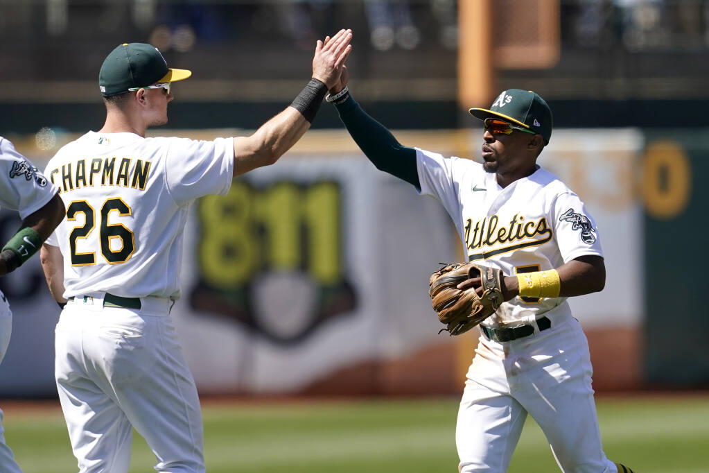 The Oakland Athletics' Matt Chapman, left, celebrates with Tony Kemp after defeating the Los Angeles Angels on Tuesday, July 20, 2021. (Jeff Chiu / ASSOCIATED PRESS)
