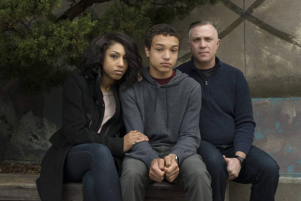 Former Analy High student Evan Mack, 16, center, with parents Raquel and John Mack photographed at Analy High School near the entrance of the school's library in Sebastopol. The family is going public because they feel Analy High School administrators have not held students of racist attacks against their son accountable for their actions. January 24, 2016. (Photo: Erik Castro/for The Press Democrat)
