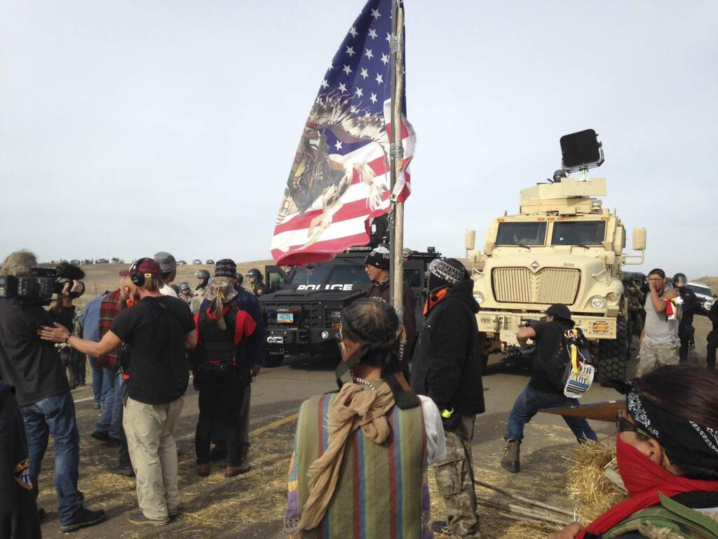Dakota Access pipeline protesters defy law enforcement officers who are trying to force them from a camp on private land in the path of pipeline construction on Thursday, Oct. 27, 2016, near Cannon Ball, N.D. The months-long dispute over the four-state, $3.8 billion pipeline reached a crisis point when the protesters set up camp on land owned by pipeline developer Energy Transfer Partners. The disputed area is just to the north of a more permanent and larger encampment on federally-owned land where hundreds of protesters have camped for months. (AP Photo/James MacPherson)