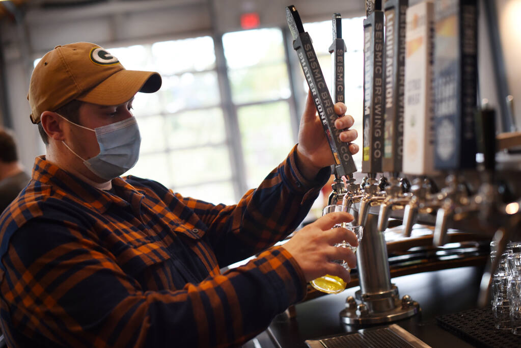 Korey Smith pours an IPA at Seismic Brewing Taproom in The Barlow in Sebastopol on Thursday, Oct. 7, 2021. (Erik Castro/for The Press Democrat)