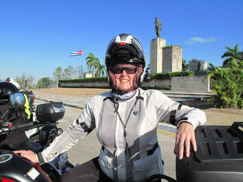 This March 2017 photo provided by Alisa Clickenger, shows Clickenger posing in front of the Che Guevara Mausoleum, a favored stop for visitors in Cuba. Clickenger operates Women's Motorcycle Tours, which conducts motorcycle rides that cater exclusively to women, and estimates she's traveled more than 250,000 miles on motorcycles. (Courtesy of Alisa Clickenger via AP)
