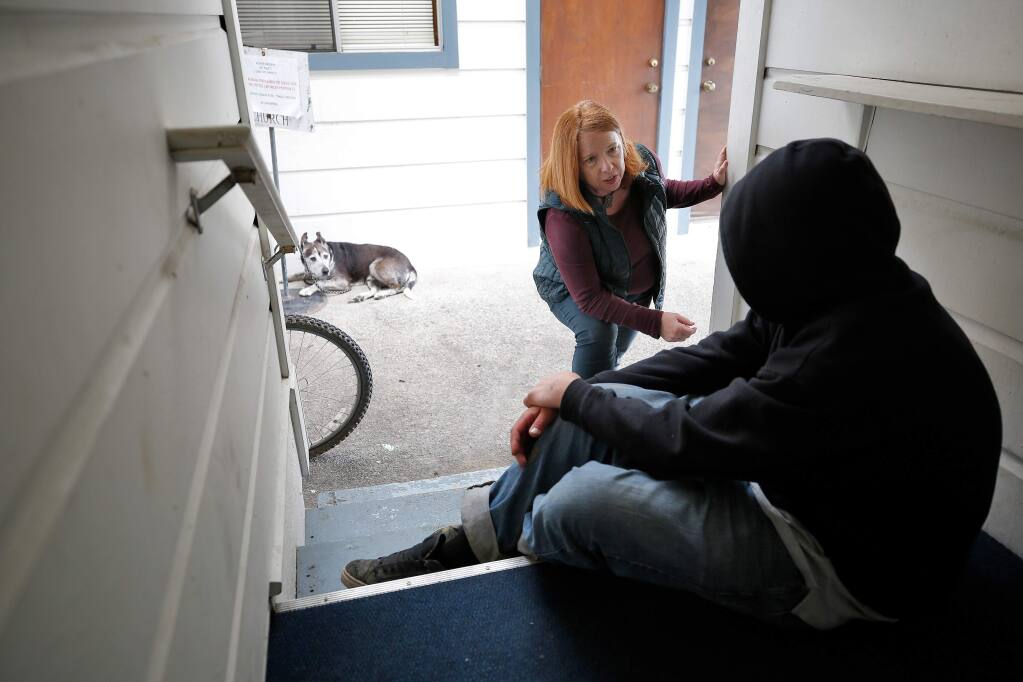 Behavioral health clinician Charmaine Rable of the Sonoma County Department of Health Services talks with Jeremiah White, who has been homeless off and on for four years, as he rests in an alcove at St. Paul's Episcopal Church in Healdsburg, California, on Thursday, March 21, 2019. (Alvin Jornada / The Press Democrat)