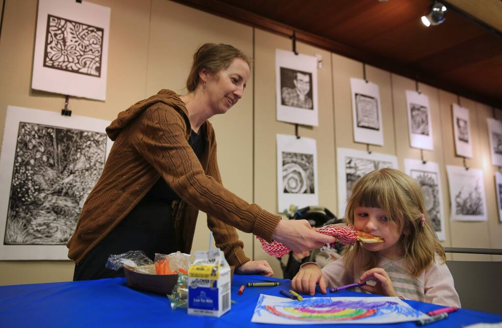 Kathleen Lennon, feeds her 4-year-old daughter, Ana, a slice of cheese pizza at the Free Summer Lunch Program, which is part of the nationwide Summer Food Service Program, at the Sebastopol Library, in Sebastopol, on Tuesday, July 5, 2016. (Christopher Chung/ The Press Democrat)