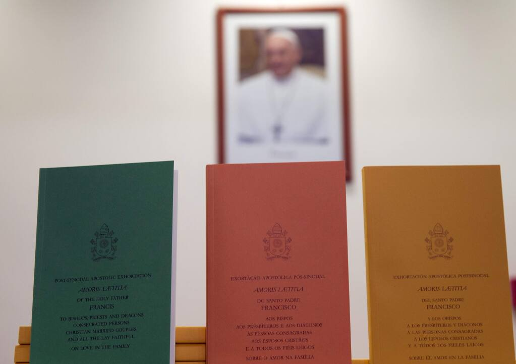 Copies of the post-synodal apostolic exhortation ' Amoris Laetitia ' (The Joy of Love) document are on display prior to the start of a press conference, at the Vatican, Friday, April 8, 2016. Pope Francis has insisted that individual conscience be the guiding principle for Catholics negotiating the complexities of sex, marriage and family life in a major document released Friday that repudiates the centrality of black and white rules for the faithful. In the 256-page document 'The Joy of Love,' released Friday, Francis makes no change in church doctrine. (AP Photo/Andrew Medichini)