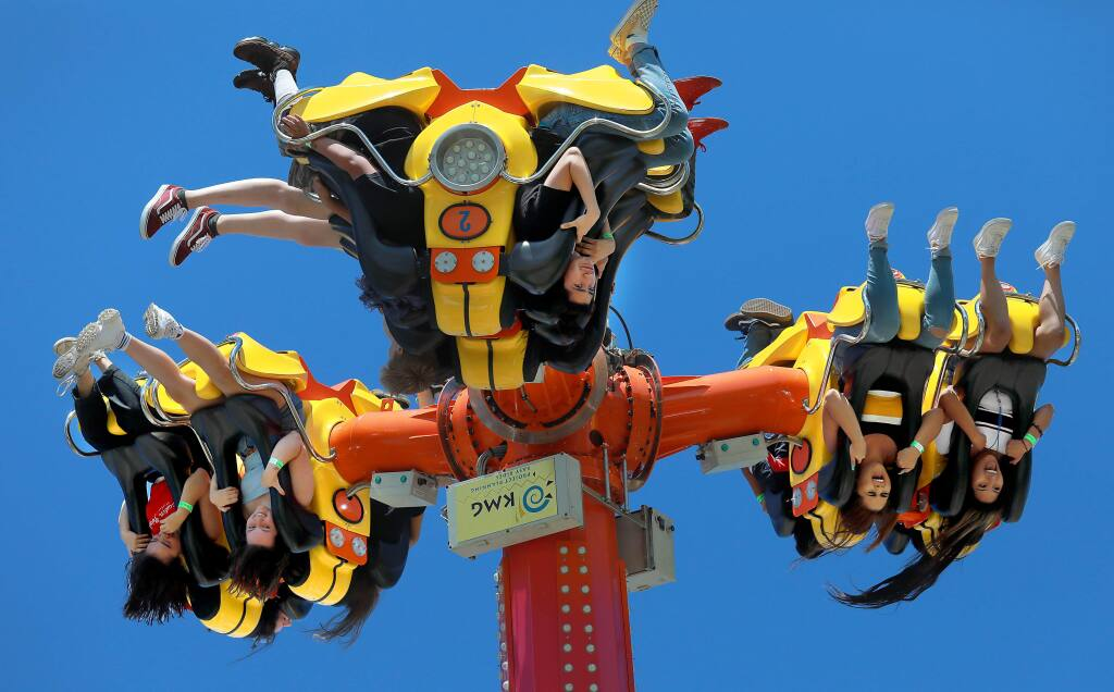 Teens scream as they turn upside down high above the midway on the Inversion ride at the opening day of the Sonoma County Fair on Friday, Aug. 2, 2018. (JOHN BURGESS/ PD)