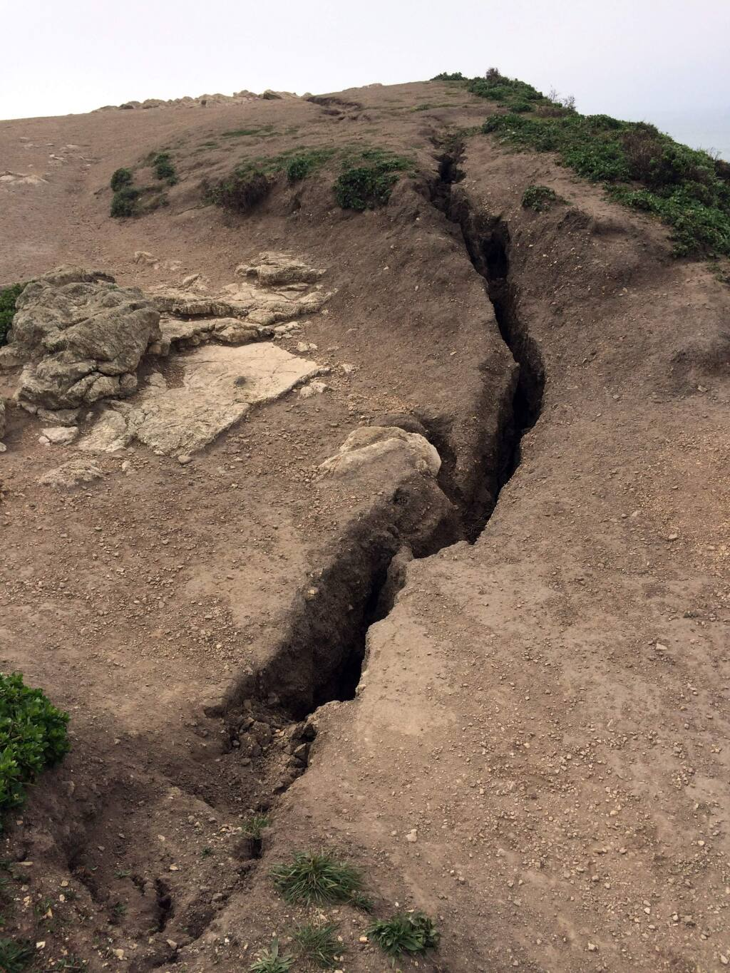 This recent but undated photo provided by Point Reyes National Seashore shows a fissure that has opened up atop Arch Rock within Point Reyes National Seashore on the Northern California coast north of San Francisco. One person is dead and another being treated for life-threatening injuries after the bluff at the end of a popular hiking trail collapsed Saturday, March 21, 2015. Two visitors were standing on the Arch Rock lookout point just before 6 p.m. when the bluff gave way. The pair fell about 70 feet and were covered with rocks and debris. One of the hikers was pronounced dead at the scene. The other was airlifted to a hospital. (AP Photo/Point Reyes National Seashore)