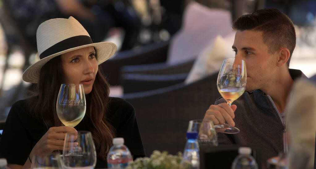 Whitney Lewis, left, and Allan Kunst taste wine at Martinelli Winery near Forestville, Friday, July 31, 2020.  (Kent Porter / The Press Democrat) 2020