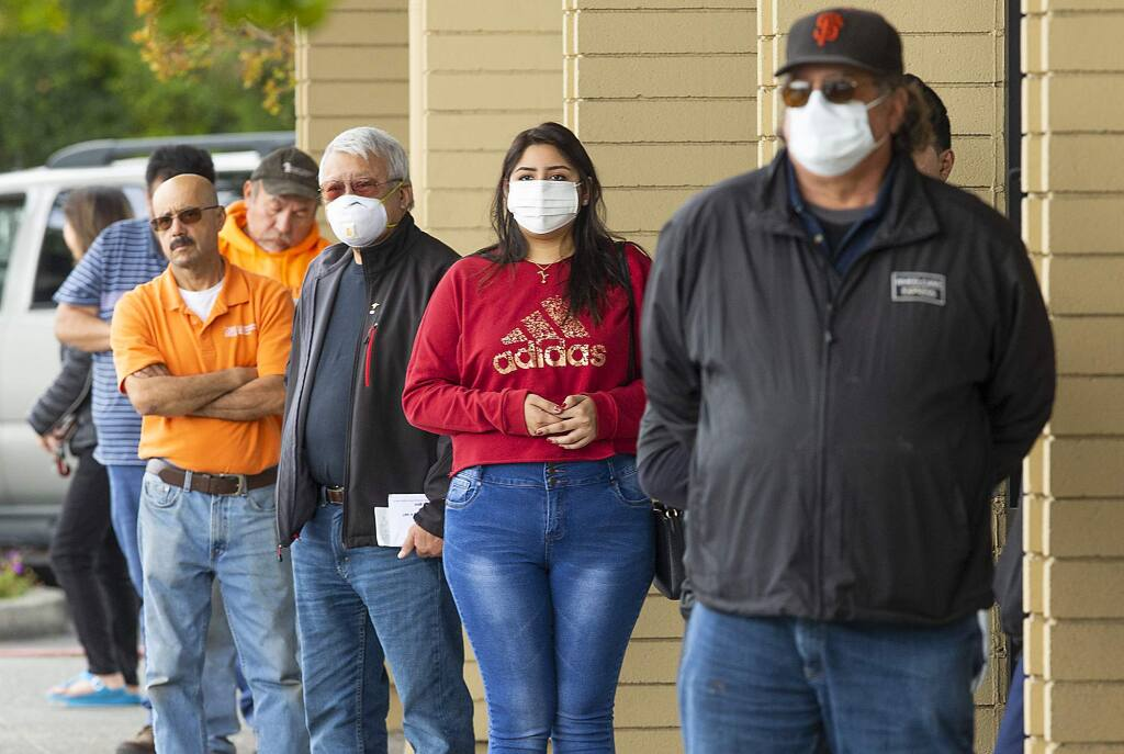 Customers line up 6 feet apart while waiting in line to get into the Wells Fargo Bank branch on Cleveland Ave. in Santa Rosa on Monday. The Centers for Disease Control has recommended people wear protective face masks when out in public. (photo by John Burgess/The Press Democrat)
