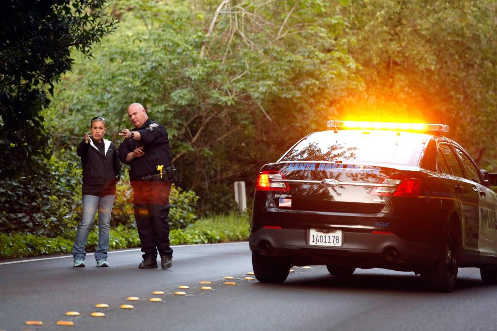 Santa Rosa Police sergeant Summer Black, left, and traffic investigator Jeff Woods investigate the scene of a fatal, single vehicle accident on Montgomery Drive, in Santa Rosa, California, on Tuesday, April 4, 2017. (Alvin Jornada / The Press Democrat)