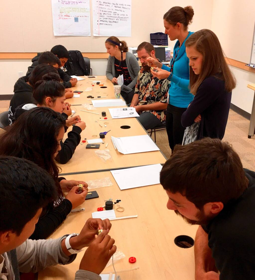 Helping Mike Hauser Algebra Academy students assemble Keysight After School solar powered cars are, left to right on the right side of the table, intern Erin Winick, Keysight employees Luke Haley and Kaelly Farnham, intern Savannah Morgan, and Keysight employee Ben Molinari.