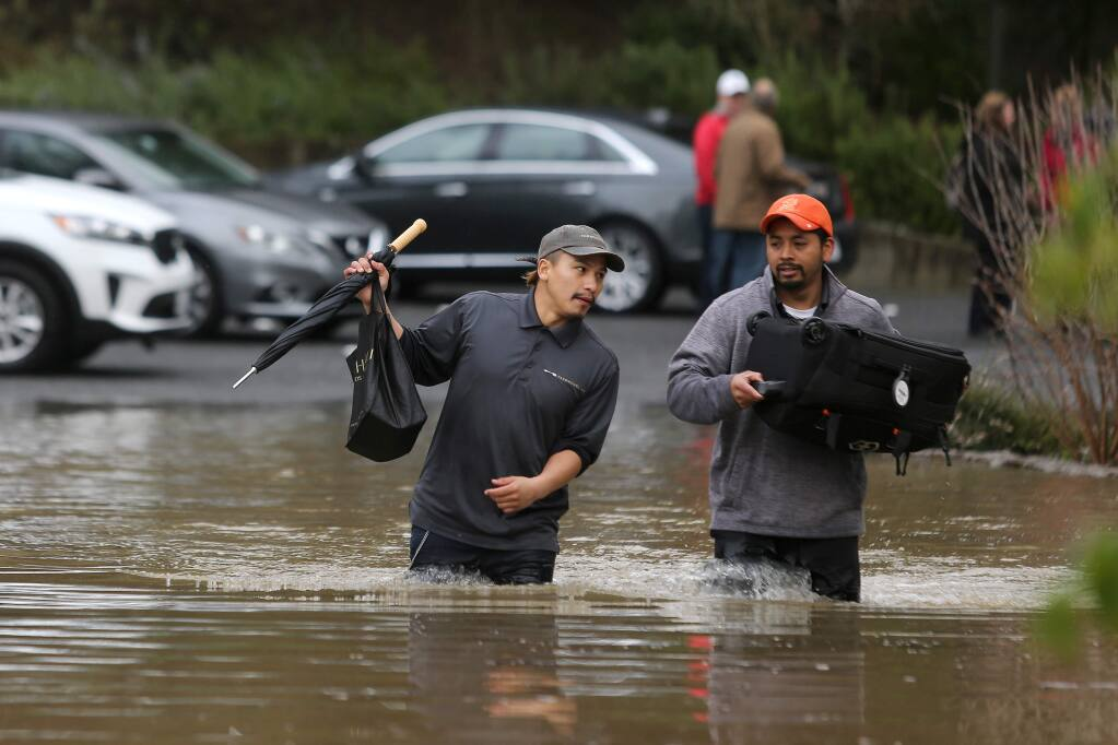 Farmhouse Inn employees Brayan Velazquez, left, and Alex Lopez help the guests with their luggage as they walk through the floodwaters at the entrance on River Road in Forestville on Wednesday, Feb. 27, 2019. (BETH SCHLANKER/ PD)
