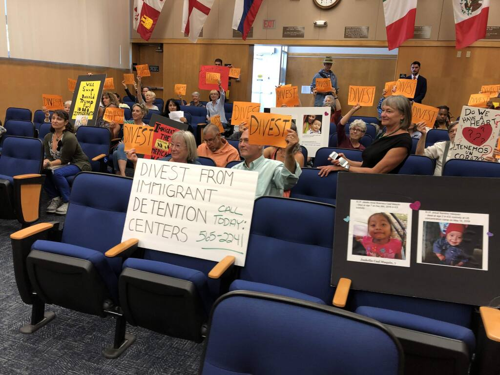 Residents hold up 'Divest' signs Tuesday before the public comment portion of a Board of Sonoma County Supervisors meeting. Residents urged supervisors to divest from U.S.-Mexico border detention facility-connected companies. (Tyler Silvy/The Press Democrat)