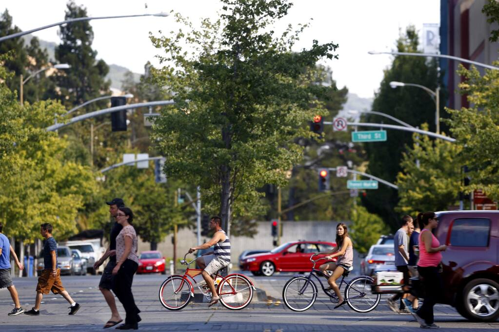 Pedestrians, cyclists and motorists cross Mendocino Avenue at Fourth Street next to Old Courthouse Square in Santa Rosa on July 13, 2014. (BETH SCHLANKER/ The Press Democrat