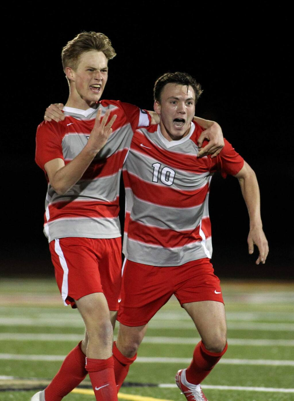 Montgomery's Kevin Welch, left, and Zack Batchelder celebrate victory at the end of their NCS soccer championship contest against Berkeley in February. (Darryl Bush / For The Press Democrat)