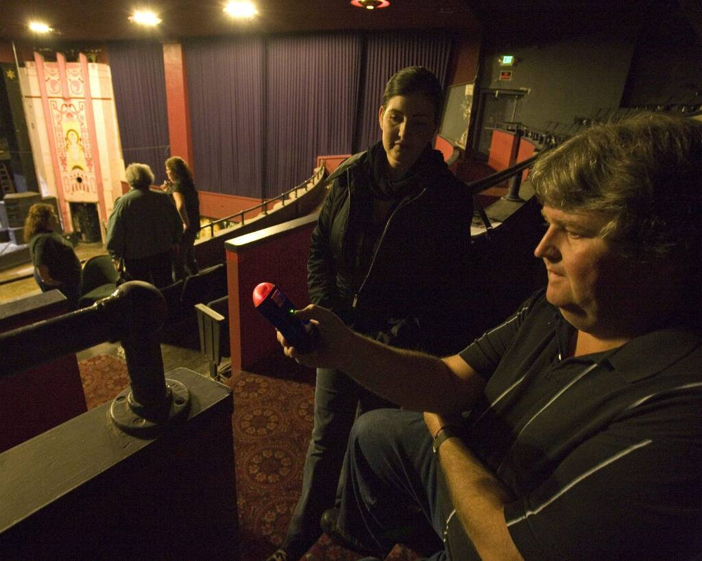 Dave Henderson and Kim Malone, both with the Pursuit of Paranormal Studies, use a meter to detect changes in electricity inside the Phoenix Theater. Photo by Terry Hankins.