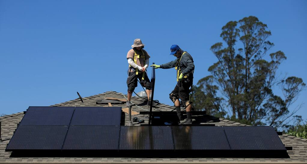 Mateo Sheerin, left, and Justin Hiner of Synergy Solar prepare to fish off the south facing aspect of a solar panel installation, Thursday, Sept. 12, 2019 in Sebastopol. (Kent Porter / The Press Democrat) 2019